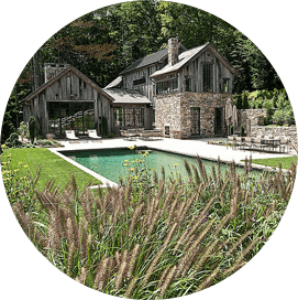 Old historic home with wood siding, brick chimney, and modern pool in backyard